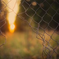 Boundary - hole in a chain link fence that symbolizes broken boundaries.