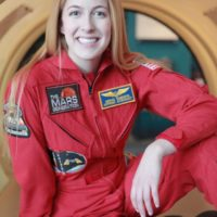 """Abigail """"Astronaut Abby"""" Harrison sits wearing a red jumpsuit with logos on it such as one reading The Mars Generation"""